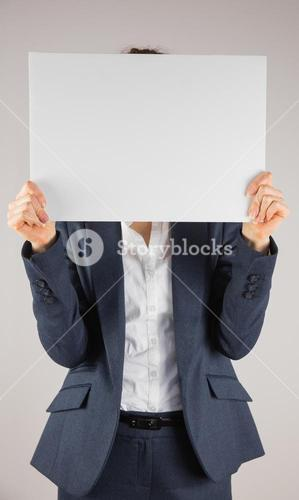 Businesswoman holding card over face
