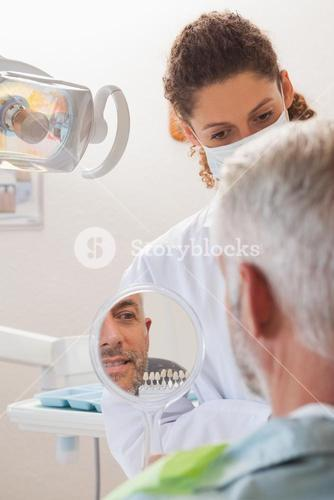 Patient admiring his new smile in the mirror