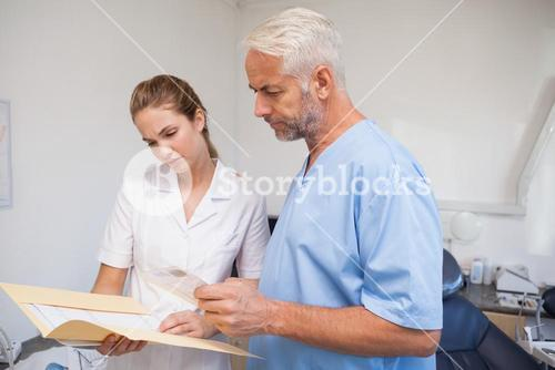 Dentist and assistant studying folder
