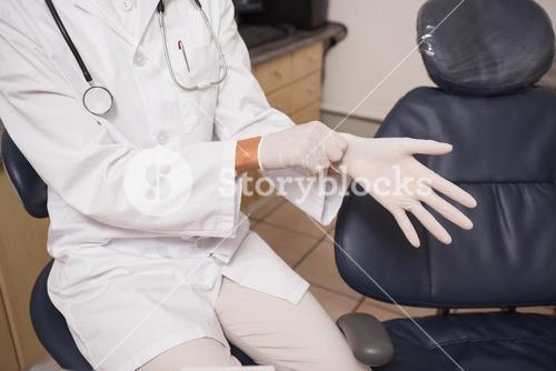 Dentist putting on surgical gloves