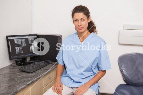 Dentist in blue scrubs looking at camera sitting at desk