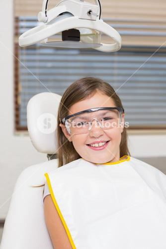 Little girl sitting in dentists chair wearing protective glasses