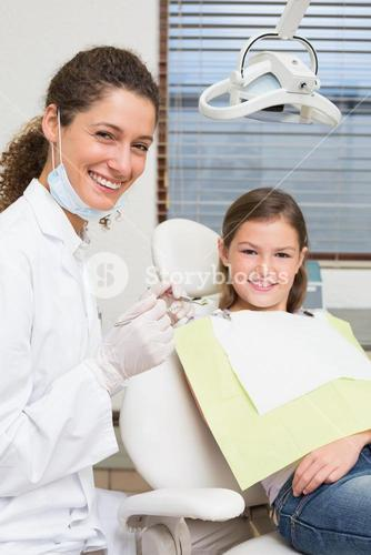 Pediatric dentist and little girl in the dentists chair smiling at camera