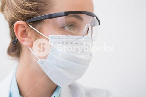 Dentist with surgical mask and protective glasses