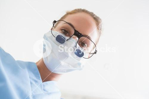 Dentist in surgical mask and dental loupes looking down over patient