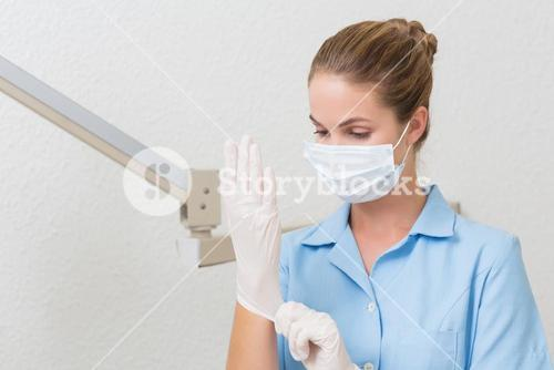 Dental assistant in mask pulling on gloves