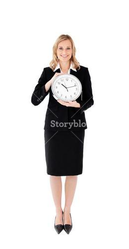 Delighted businesswoman holding a clock against white blackground