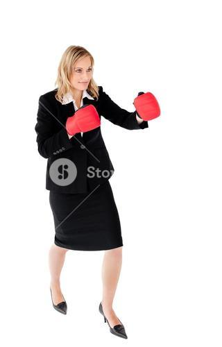 Selfassured businesswoman with red boxing gloves against white background