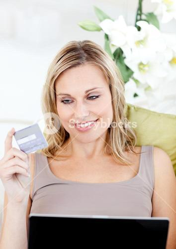 Delighted woman holding a card and a laptop