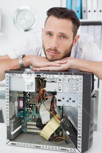 Sad computer engineer leaning on computer