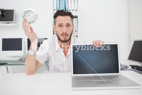 Confused computer engineer looking at camera with laptop
