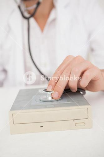 Computer engineer listening to harddrive with stethoscope