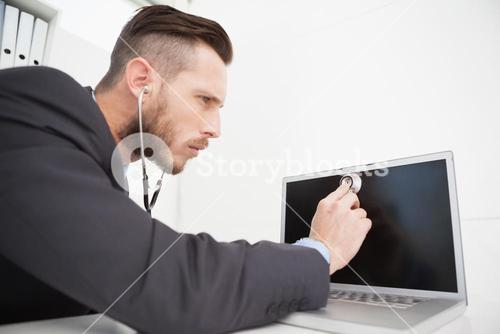 Businessman listening to laptop with stethoscope