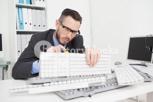 Technician fixing keyboard with screw driver