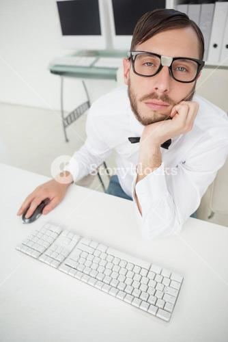 Nerdy bored businessman working on computer