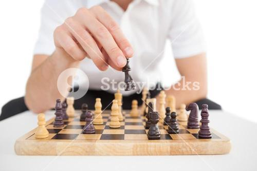 Focused businessman playing chess solo