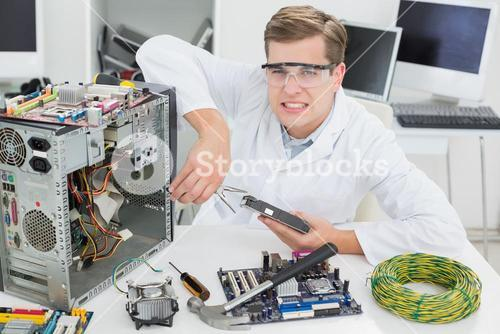 Angry computer engineer working on broken device