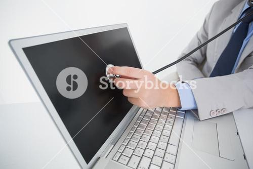 Technician listening to laptop with stethoscope