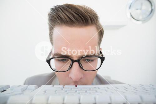 Nerdy businessman looking at keyboard