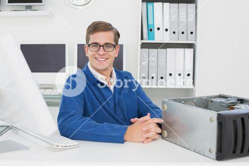 Smiling technician sitting at desk