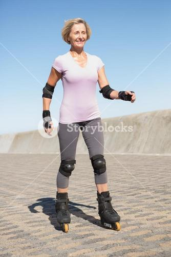 Active senior woman rollerblading on the pier