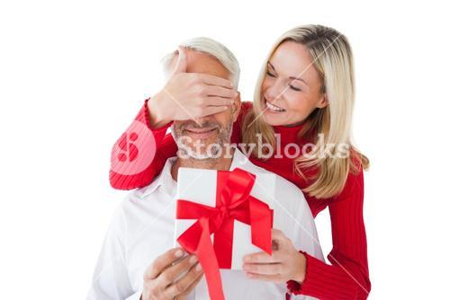 Smiling woman covering partners eyes and holding gift
