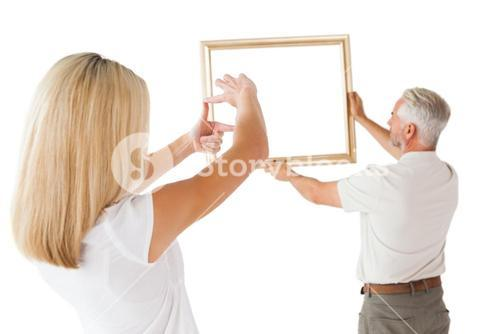 Couple hanging a frame together