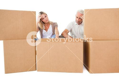 Stressed couple looking at moving boxes