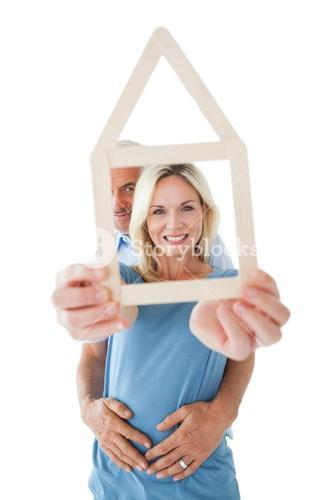 Happy couple holding house outline