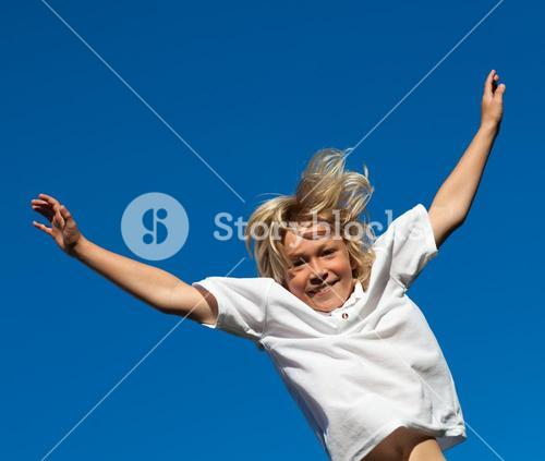 Smiling Kid Jumping in the air outdoor