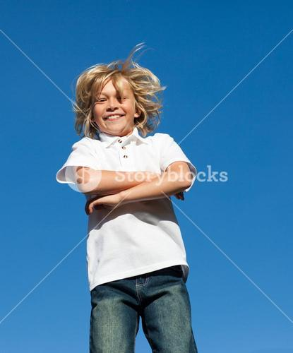 Blond Kid Jumping in the air outdoor