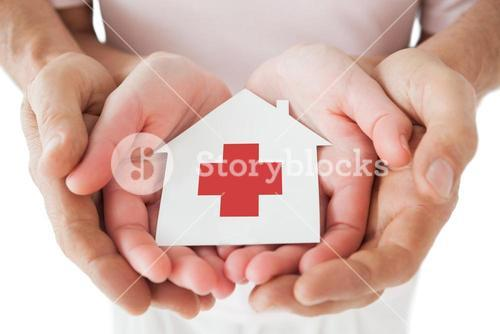 Couple holding paper house with red cross in hands