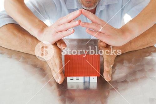 Couple sheltering miniature house with hands