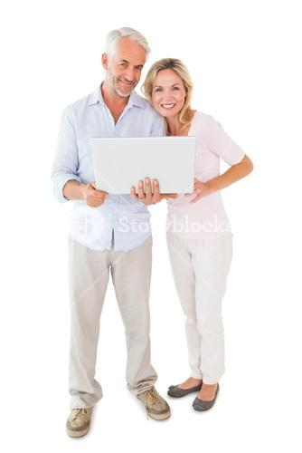Happy couple standing and using laptop together