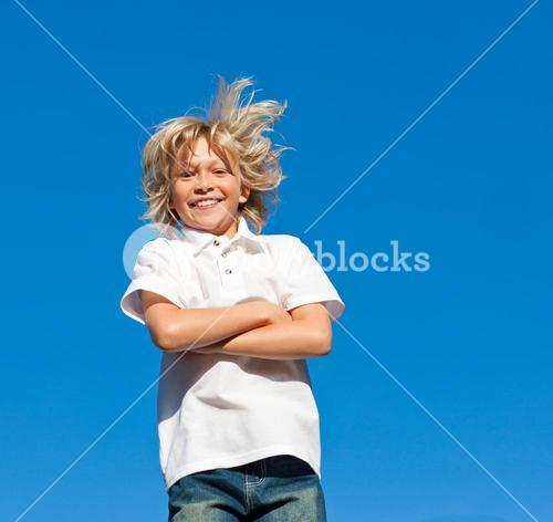 Joyful Kid with arms folded having fun outdoor