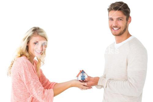 Attractive couple holding miniature house model