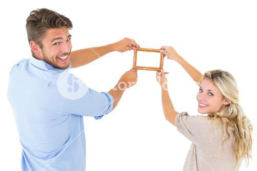 Attractive young couple hanging a frame