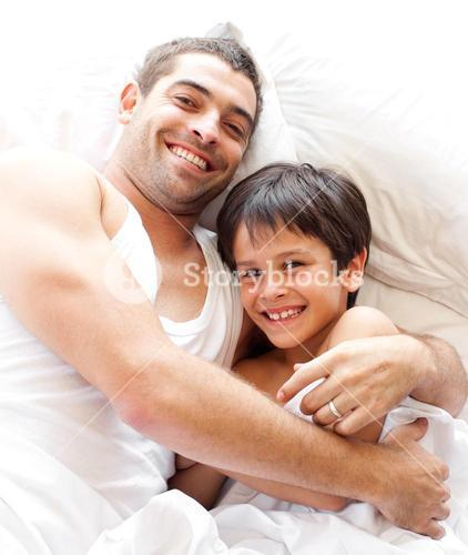 Bright father and son smiling at camera
