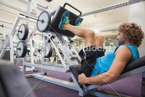 Handsome man doing leg presses in gym