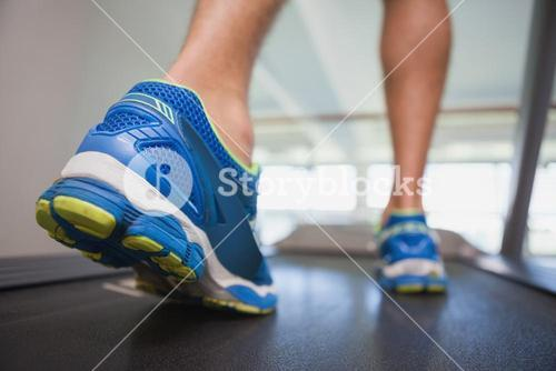 Low section of a man running on treadmill