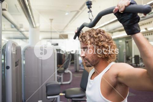 Young man exercising on a lat machine in gym