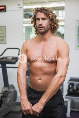 Shirtless man exercising with kettle bell