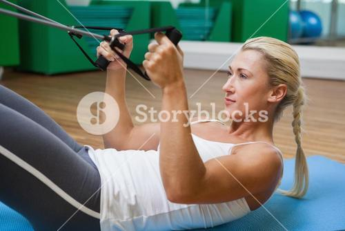 Sporty woman using resistance band in fitness studio
