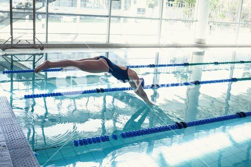 Side view of swimmer diving into pool at leisure center