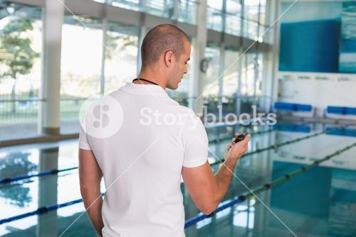 Swimming coach looking at stopwatch by pool at leisure center