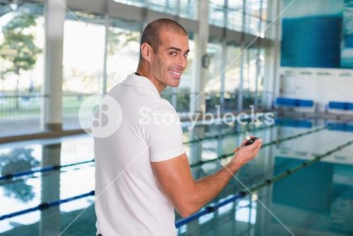 Swimming coach with stopwatch by pool at leisure center