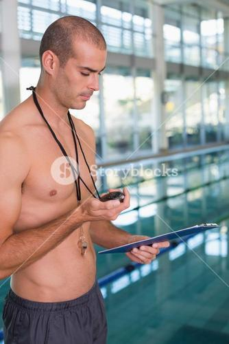 Shirtless coach with stopwatch by pool at leisure center