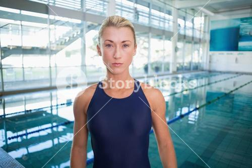 Female swimmer by pool at leisure center
