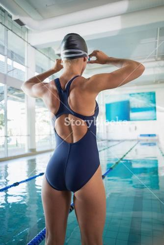 Rear view of a female swimmer by pool at leisure center