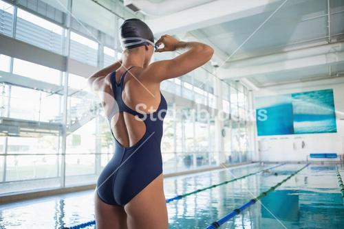 Rear view of a fit swimmer by pool at leisure center